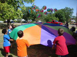 kids bouncing balls with a parachute